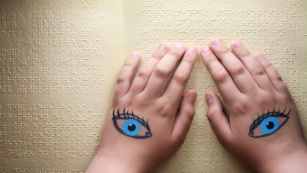 Article santé magazine : mains lisant du braille, des yeux sont dessinés sur les mains